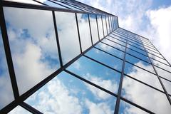 reflecting clouds in glass facade - stock photo