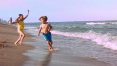 Two Little Kids Play In The Waves, Run Back And Forth Happily - stock footage