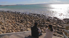 Sunshine Coast - 1 minute two young people chat and enjoy the beach Stock Footage