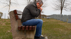 Man with walking stick on bench in the cemetery Stock Footage