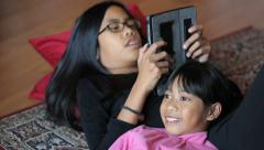 Teenage Girl Reads Book To Little Sister Off Tablet Stock Footage