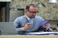 Businessman compare results on cellphone tablet and laptop. Stock Footage