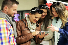 Friends looking on cellphone and smiling, steadycam shot. Stock Footage