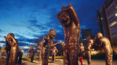 Dusk Time-lapse of Public Art Statues (A-maze-ing Laughter) in English Bay Stock Footage