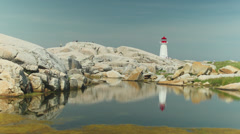 Famous Lighthouse at Peggy's Cove, Nova Scotia, with Reflection. Stock Footage