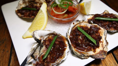 Oysters Kilpatrick Restaurant food Stock Footage