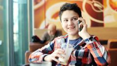 Stock Video Footage of Young teenager talking on cellphone and drinking milkshake in cafe HD