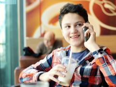Stock Video Footage of Young teenager talking on cellphone and drinking milkshake in cafe NTSC
