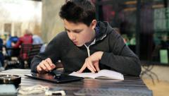 Young boy with tablet computer doing homework in cafe HD Stock Footage