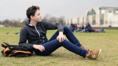 Young teenage student relaxing in the park HD Stock Footage