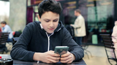 Young teenage boy texting on smartphone in cafe HD - stock footage