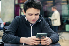 Young teenage boy texting on smartphone in cafe NTSC - stock footage
