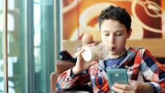 Stock Video Footage of Young teenage boy texting on smartphone and drink milkshake in cafe HD