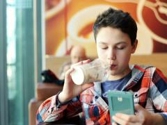 Young teenage boy texting on smartphone and drink milkshake in cafe NTSC - stock footage