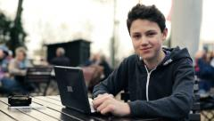 Happy young teenager with laptop sitting in cafe HD Stock Footage