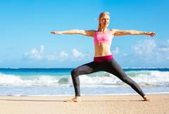 athletic fitness woman stretching at the beach, - stock photo