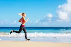 Athletic fitness woman running on the beach Stock Photos