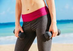 Close-up of torso of fitness woman holding barbells Stock Photos