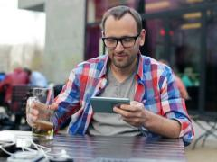 Young student texting on smartphone, drink beer in cafe NTSC - stock footage