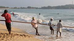 Fishermen on beach hauling in a large fishing net Stock Footage