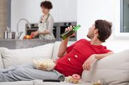 Stock Photo of couch potato doesn't help wife