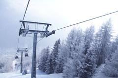 Chair lift between beautiful firs in winter mountains Stock Photos