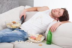 Stock Photo of alcoholic sleeping on couch