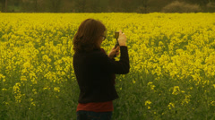 Female photographer in Rapeseed Field (slow motion) Stock Footage