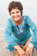 Brunet woman in blue dress on the beach Stock Photos