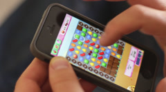 "Editorial: Playing the popular app game ""Candy Crash"" on a smartphone Stock Footage"