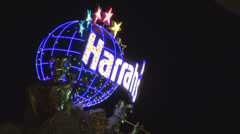 Harrahs illuminated neon sign Las Vegas Strip resort hotel casino luxury gamble  Stock Footage