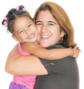 Mother hugging her small multiracial daughter Stock Photos