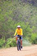 Young man riding mountain bike in dusty road Stock Photos