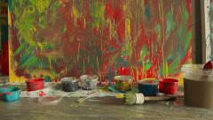 Dolly shot of a paints and brushes on the background of multicolored canvas - stock footage