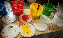 Colorful paint buckets with brushes and color spots on the table Stock Photos