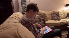 Teenage boy holding a tablet computer on his lap, typing a message, email - stock footage