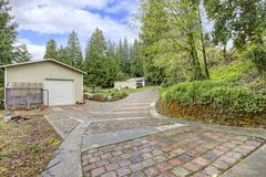 view of the garage and  stone driveway - stock photo
