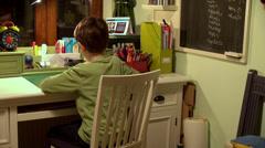 Little school boy, pupil, child on his desk doing homework Stock Footage