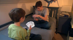 Two brothers playing cards at home, boys enjoying game, having fun Stock Footage