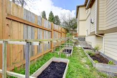 Small backyard garden bed wih wooden trellis and grid Stock Photos