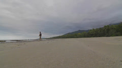 A wide low angle of man walking in distance at a beach in Cape tribulation Stock Footage