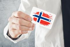 Norwegian businessman holding business card with norway flag Stock Photos