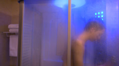 Teenage boy taking a shower, young man washing his body, hygiene - stock footage