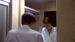 Good looking teenage boy with new haircut looking in mirror and washing face Stock Footage