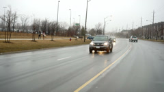 Driving down a rainy wet road with oncoming traffic Stock Footage
