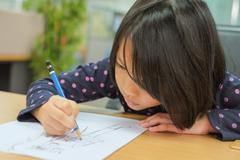 Cute little girl is drawing cartoon Stock Photos