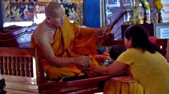 Buddhist monk blessing a woman - Bangkok Stock Footage