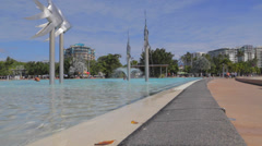 Pan -  people walking and in the pool at cairns esplanade Stock Footage