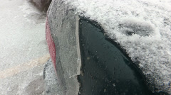 College students scrape ice off cars in winter ice storm Stock Footage