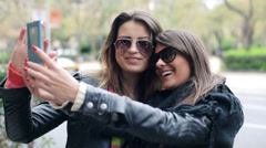 Stock Video Footage of Two happy girlfriends taking photo with their smartphone in the city HD